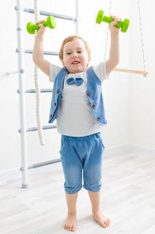 집에서 아기 스포츠, 귀여운 소년 리프트 아령, 스포츠 및 어린이 건강의 개념