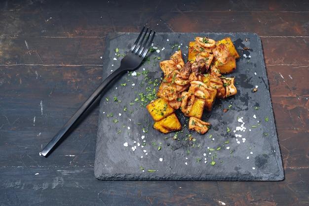 スペイン料理の典型的なスターターであるニンニクとジャガイモを添えたスペインのイカまたはチピロンの赤ちゃん