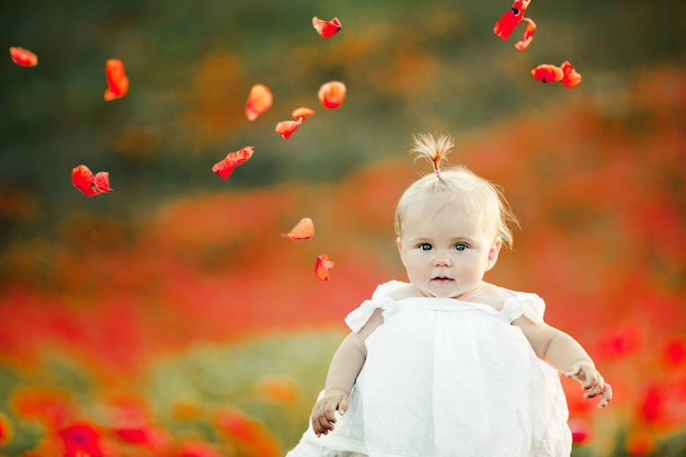 A baby stands among poppy field