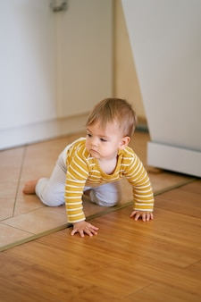Baby in a striped blouse and pants crawls from a tile to a laminate in the kitchen