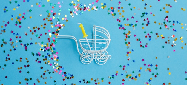 Baby stroller with a candle in the form of the number one on a blue background