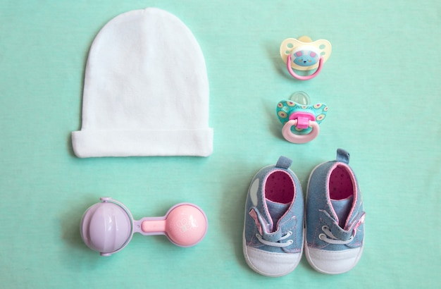 Baby stuff is on a blue background. top view closeup. things little girl, pacifier, rattle, hat, and shoes.newborn baby necessities