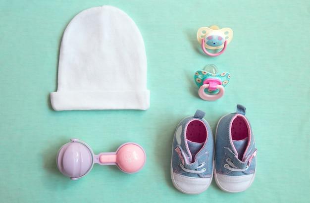 아기 물건은 파란색 배경입니다. 상위 뷰 근접 촬영. 어린 소녀, 젖꼭지, 딸랑이, 모자 및 신발. 신생아 필수품