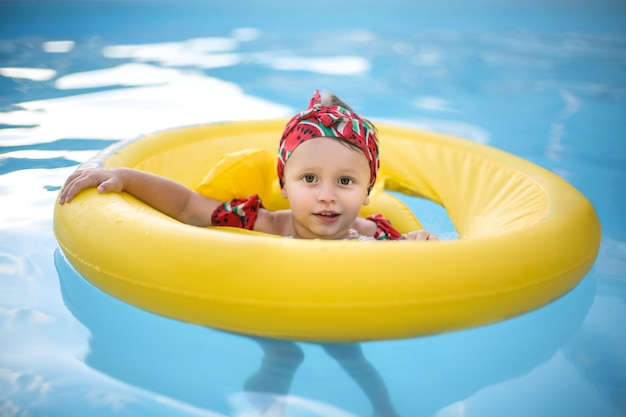 Baby swimming in the swimming pool with an inflatable boat