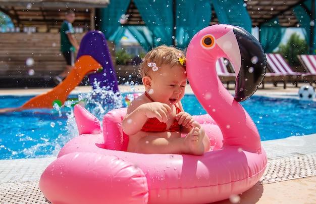 아기는 수영장에서 원을 그리며 수영합니다. 선택적 초점입니다. 아이.