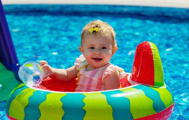 赤ちゃんはプールで輪になって泳ぎます。セレクティブフォーカス。子供。