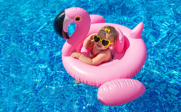 赤ちゃんはプールで輪になって泳ぎます。セレクティブフォーカス。自然。