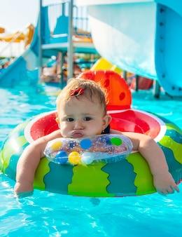 赤ちゃんはプールで輪になって泳ぎます。セレクティブフォーカス。