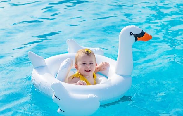 赤ちゃんは海のゴムリングで泳ぐ Premium写真