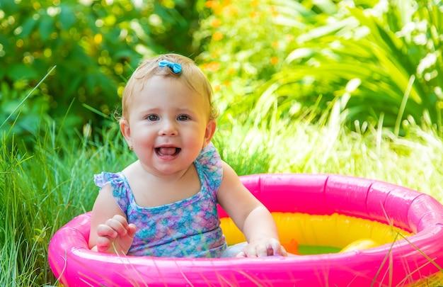 赤ちゃんはプールで泳ぎます。セレクティブフォーカス。