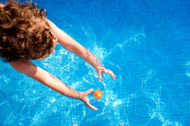 Baby swims in a pool trying to reach a toy in the water, top view in summer.