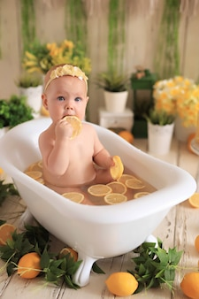 Baby taking a bath with lemons surrounded by plants