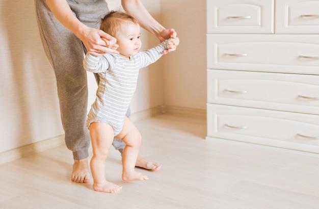 寝室で母親の助けを借りて最初の一歩を踏み出す赤ちゃん