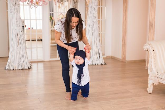 母親の助けを借りて最初の一歩を踏み出す赤ちゃん、