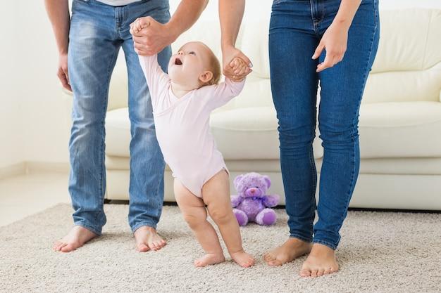 家で母親と父親の助けを借りて最初の一歩を踏み出す赤ちゃん。