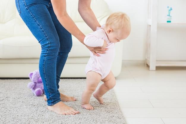 집에서 엄마의 도움으로 첫 발을 내딛는 아기
