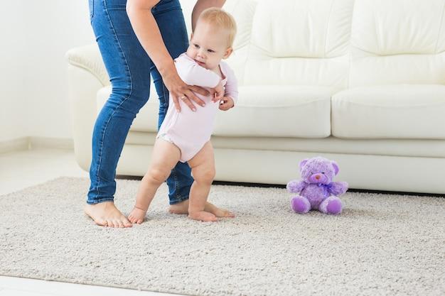 自宅で母親の助けを借りて最初の一歩を踏み出す赤ちゃん