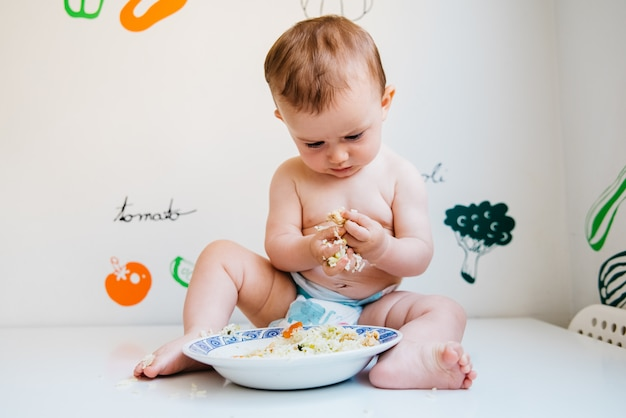 Baby taking handfuls of food to put in his mouth and eat them.