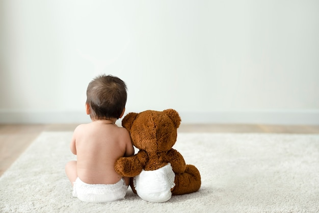 Baby and teddy bear rear view with design space