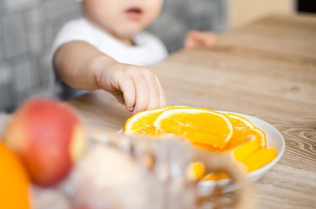 Ребенок на кухне хочет взять дольку апельсина, пытаясь протянуть руку