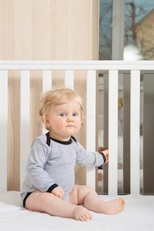 Baby toddler in baby crib.