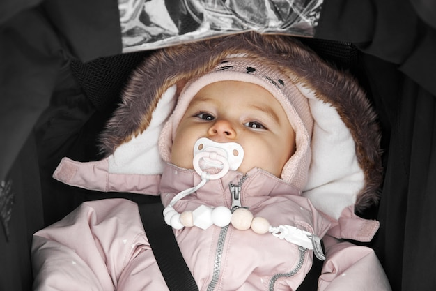 Baby toddler in balck stroller outdoors on a snowy winter dayin sonwsuit