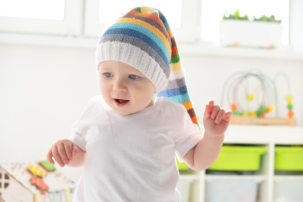 Baby toddler boy in funny hat is learning to walk at home.