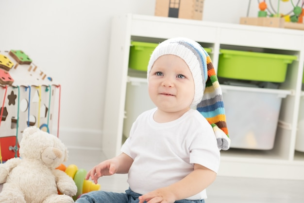 Baby toddler boy playing with busy board and teddy bear at home. developing games for children.