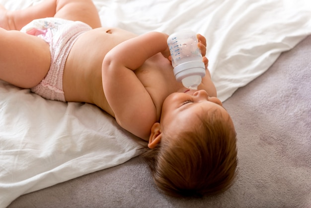 Baby toddler laying on the white bed, smiles and drinks water from plastic bottle