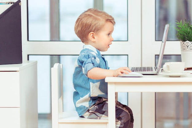 自宅のコンピューターで遊んで笑っている幼児、子供たちは新しいデジタルテクノロジーとガジェットが大好きです