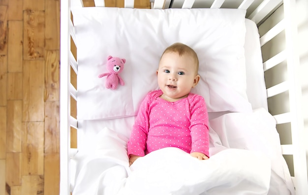 아기 유아는 침대에서 재생됩니다. 선택적 초점. 아이.