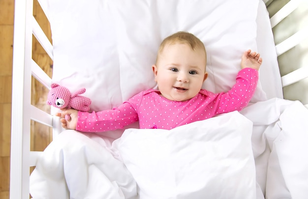 아기 유아는 침대에서 재생됩니다. 선택적 초점.