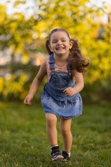 家の近くの緑の芝生の上を走っている幼児