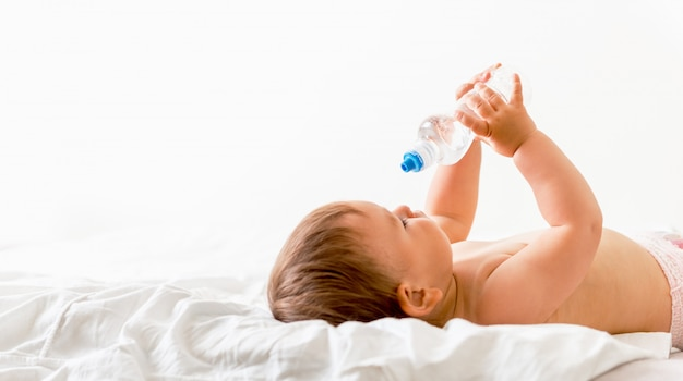 Baby toddler sits on the white bed, smiles and drinks water from plastic bottle