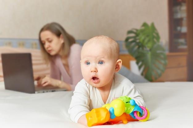 自宅でラップトップコンピューターを使用してママの実業家の近くに座っている赤ちゃん幼児。水平画像、正面図