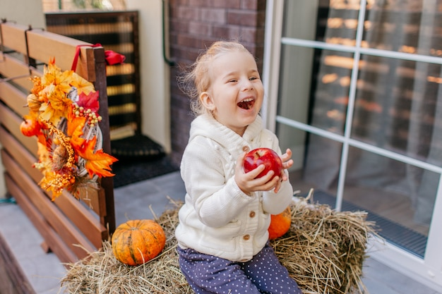 Baby toddler in white knittes jacket sitting on the haystack with pumpkins at porch, playing with apple and laughing