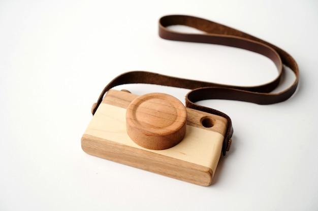 복사 공간 흰색 표면에 아기 장난감 사진 카메라. 가죽 끈이 달린 나무 카메라 장난감