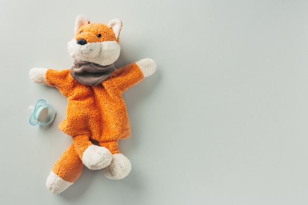 Baby toy red fox and nipple on pastel