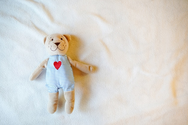Baby toy teddy bear with heart, light childhood with empty place for text. copy space