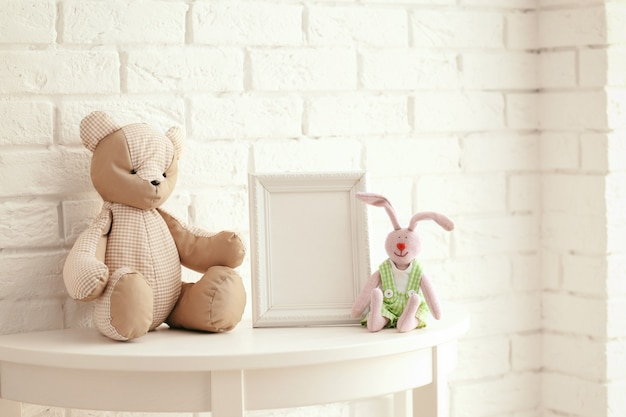 Baby toys and frame on brick wall background