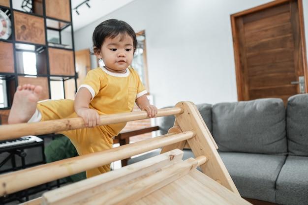 거실에 있는 삼각형 장난감 피클러에 올라타면서 다리를 들어 올리려고 하는 아기