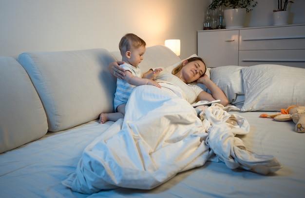 ベッドで寝ている疲れた母親を起こそうとしている赤ちゃん