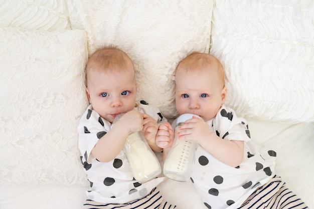 Baby twins lie on the bed in their pajamas and drink milk from bottles