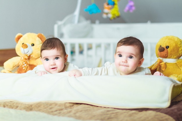 Baby twins playing on the bed