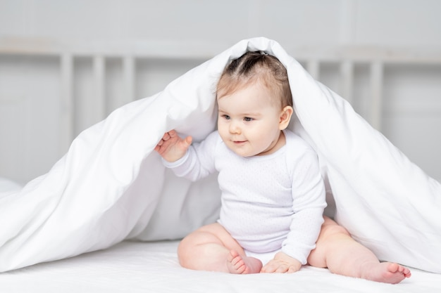 Ребенок под одеялом на кровати дома, концепция семьи и детей