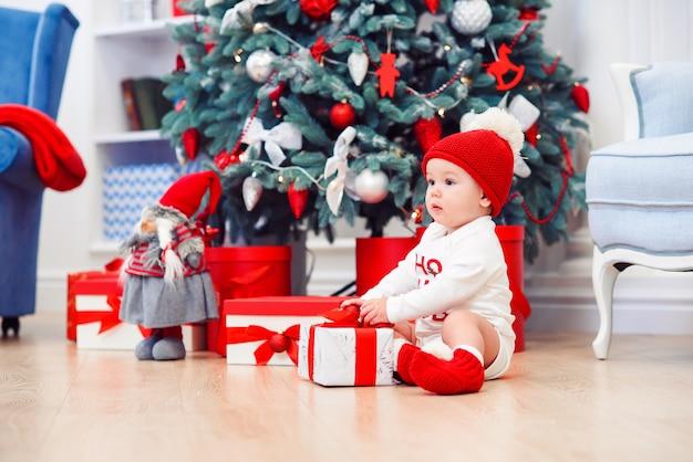 Ребенок распаковать подарочные коробки с рождественские украшения, одетые как санта, боке огни, концепция зимнего отдыха