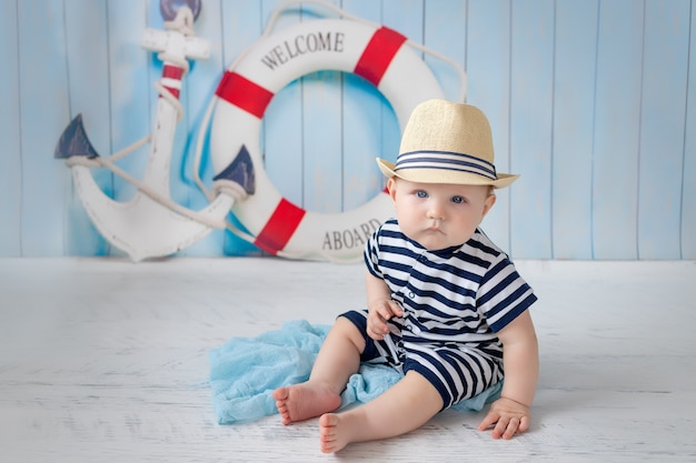 A baby in a vest next to an anchor and a lifebuoy