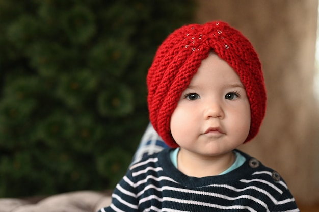 Baby and a warm hat. one year old child portrait. close-up.