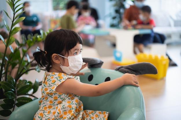 병원 테이블에 앉아 수술용 마스크를 쓴 아기