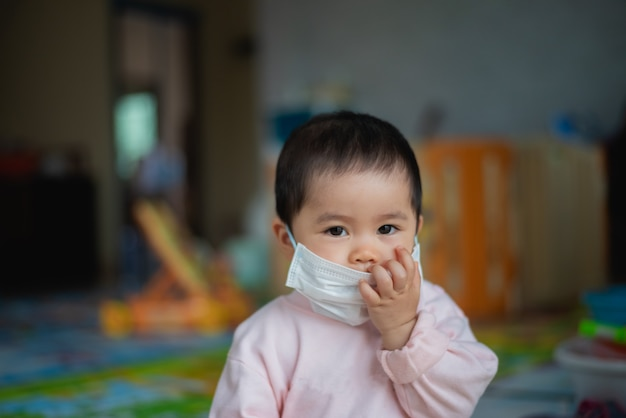 手術用マスクを身に着けている赤ちゃんは家にいます。 covid-19コロナウイルスのコンセプト
